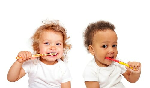 Two babies brushing teeth